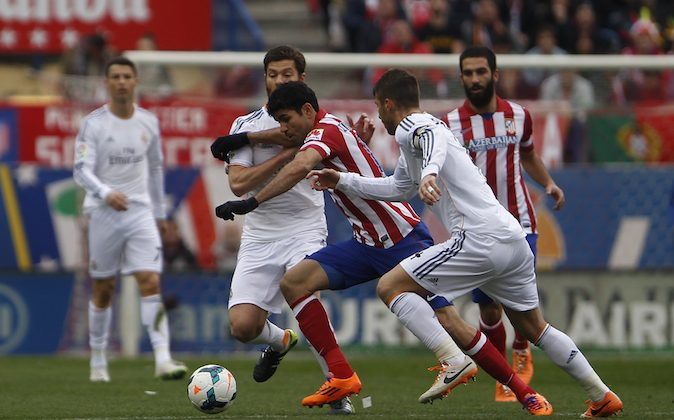Atletico's Diego Costa, center, in action with Real's Xabi Alonso, left, during a Spanish La Liga soccer match between Atletico de Madrid and Real Madrid at the Vicente Calderon stadium in Madrid, Spain, Sunday, Mar. 2, 2014. (AP Photo/Gabriel Pecot)