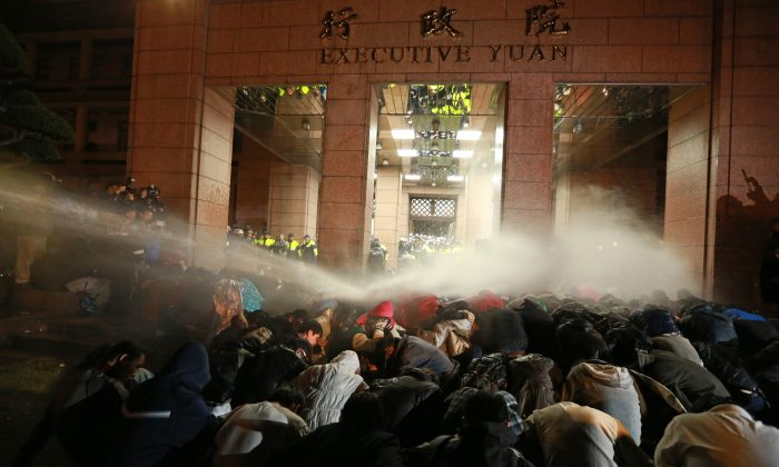 Protesters are sprayed by a water cannon during a demonstration outside the Executive Yuan in Taipei early on March 24. The protests followed Taiwan President Ma Ying-jeou's refusal to scrap a contentious trade agreement with China. (STR/AFP/Getty Images)
