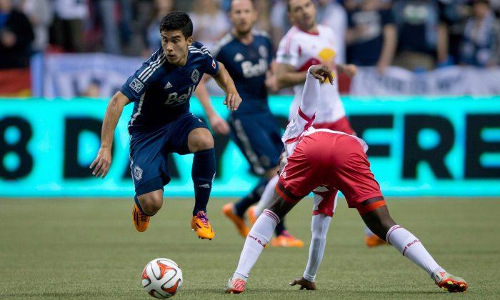 Vancouver's Uruguayan midfielder Sebastian Fernandez evades New York's French striker Peguy Luyindula as MLS kicked off in Vancouver, Canada on Mar. 8, 2014. (The Canadian Press/Darryl Dyck)