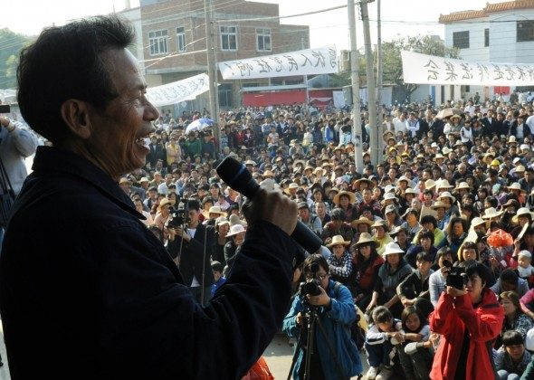 Zhuang Liehong, a village leader from Wukan, Guangdong, has asked for asylum in the United States, fearing he too will be arrested, after two other leaders were arrested recently. Villagers listen to a speech by Wukan village leader Lin Zuluan (L) at a rally on Dec. 21, 2011. (Mark Ralston/AFP/Getty Images)