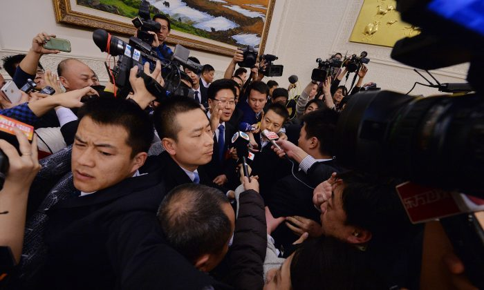 Journalists mob Xinjiang Communist Party Secretary Zhang Chunxian (center with glasses) as they try to ask questions about the recent terror attack in Kunming at the Great Hall of the People in Beijing on March 6, 2014. (Mark Ralston/AFP/Getty Images)