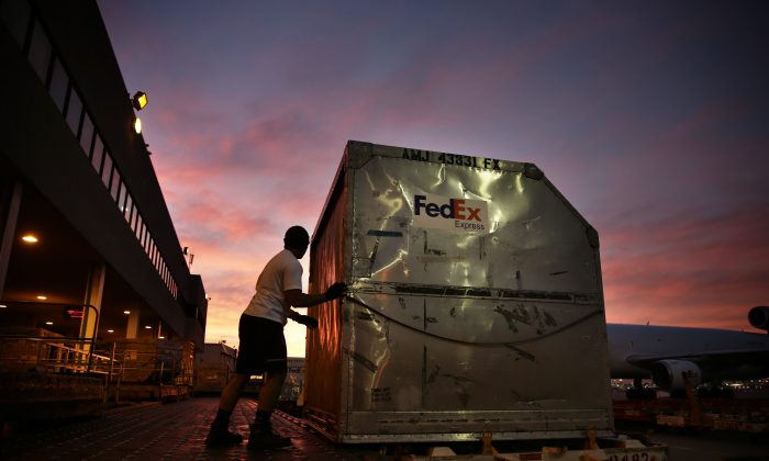 In this Monday, Dec. 2, 2013, file photo, a worker loads a container onto a FedEx cargo plane at the FedEx hub at Los Angeles International Airport in Los Angeles. (AP Photo/Jae C. Hong, File)