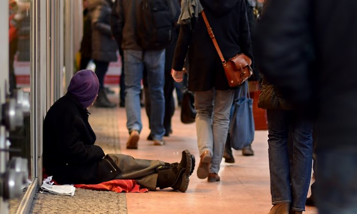 "A man begging for money sits on the pavement in Berlin, on Dec. 20, 2012. Some Romanians are being lured to Germany on false promises to beg on the streets for ""employers."" (Britta Pedersen/AFP/Getty Images)"