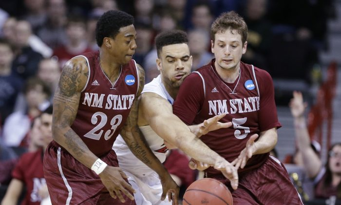 San Diego State's JJ O'Brien, center, is caught between New Mexico State's Daniel Mullings (23) and Kevin Aronis (5) in overtime during the second round of the NCAA men's college basketball tournament in Spokane, Wash., Thursday, March 20, 2014. San Diego State won 73-69. (AP Photo/Elaine Thompson)