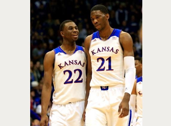 Andrew Wiggins #22 of the Kansas Jayhawks talks with Joel Embiid #21 as they walk onto the floor after a timeout during the game against the Towson Tigers at Allen Fieldhouse on November 22, 2013 in Lawrence, Kansas. (Jamie Squire/Getty Images)
