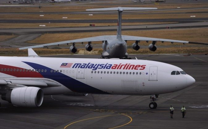 A Malaysia Airlines plane, foreground, prepares to go out onto the runway and passes by a stationary Chinese Ilyushin 76 aircraft at Perth International Airport  in Perth, Australia, Tuesday, March 25, 2014. (AP Photo/Greg Wood, Pool)