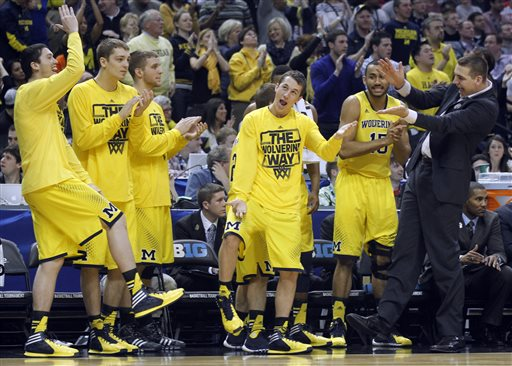 Michigan players dance around on the sideline as they react to a play in the second half of an NCAA college basketball game against Ohio State in the semifinals of the Big Ten Conference tournament Saturday, March 15, 2014, in Indianapolis. Michigan won 72-69. (AP Photo/Kiichiro Sato)