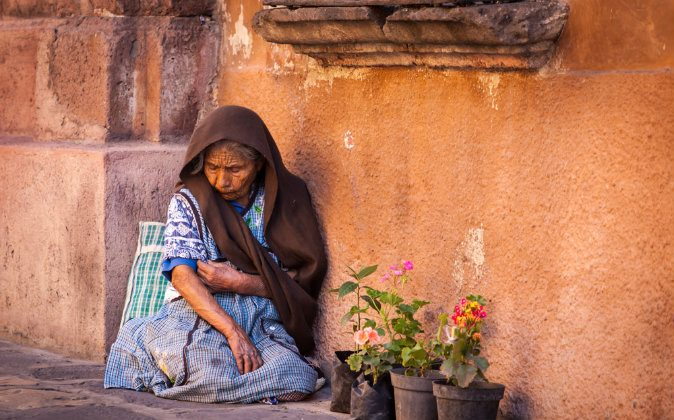 A file photo of an impoverished woman in San Miguel de Allende, Mexico. A Panama Newsroom article explores the impact of environmental policies on the poor who may bear the burden of having to pay for energy sources they can't afford.