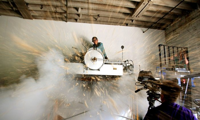 """Museum of Food and Drinks members test the puffing gun—a 3,200-pound machine that """"explosively puffs food."""" (Courtesy of Paul Adams)"""