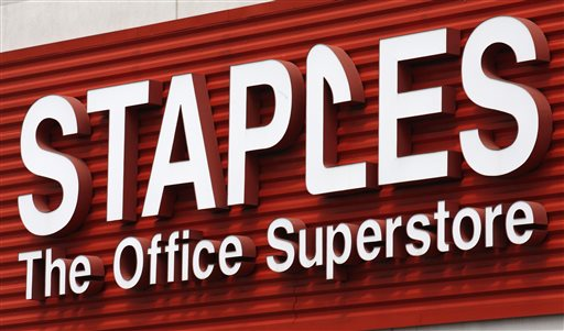 In this May 17, 2011 file photo, a Staples sign is displayed on the front of a Staple store, in Portland, Ore. Staples says it will shutter 225 North American stores, about 10 percent of Staples Inc.'s worldwide total of 2,200, by the end of 2015, and the office-supply retailer has started a plan to save about $500 million annually. (AP Photo/Rick Bowmer, File)