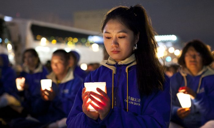 Falun Dafa practitioners hold a candlelight vigil as a peaceful protest near the Chinese Consulate in New York, on April 25, 2014. The protest is against the Chinese regime's 15-year persecution of the practice. (Samira Bouaou/Epoch Times)
