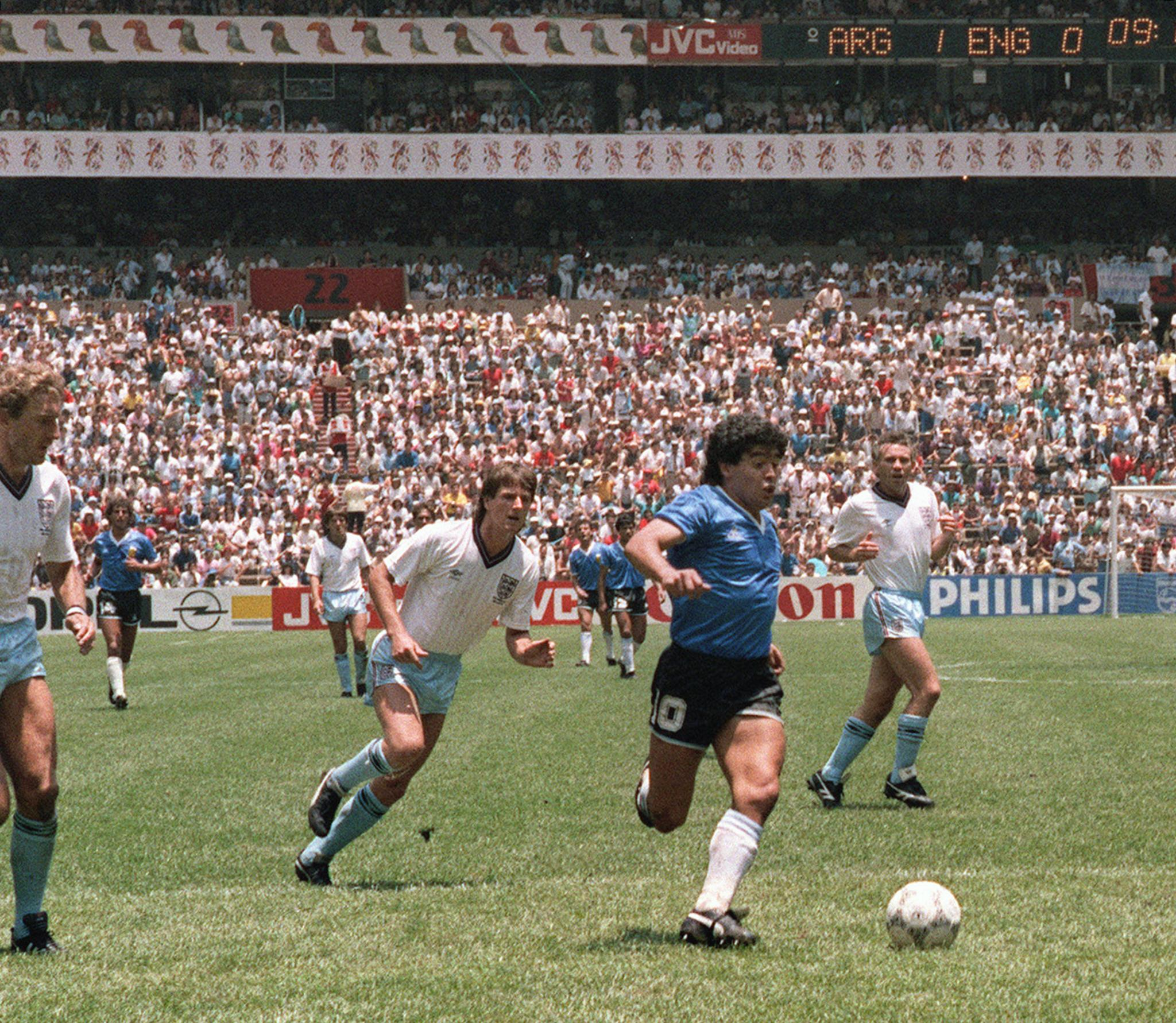 Argentinian forward Diego Armando Maradona runs past English defenders Terry Butcher (L) and Terry Fenwick (2nd L) on his way to scoring his second goal during the World Cup quarterfinal soccer match between Argentina and England 22 June 1986 in Mexico City. (AFP/Getty Images)