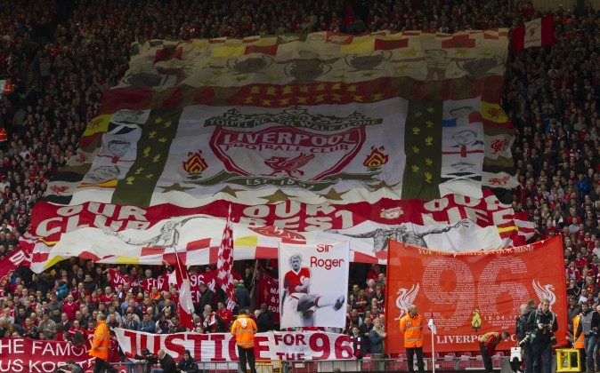 Liverpool supporters hold banners prior to a minute's silence in tribute to the 96 supporters who lost their lives in the Hillsborough disaster of 25 years ago on 15 April 1989, Liverpool, England, Sunday April 13, 2014. (AP Photo/Jon Super)