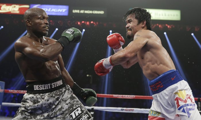 Timothy Bradley, leans back as Manny Pacquiao, of the Philippines, throws a punch during their WBO welterweight title boxing fight Saturday, April 12, 2014, in Las Vegas. (AP Photo/Isaac Brekken)