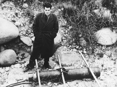 "John Whiteside ""Jack"" Parsons standing above a jet-assisted take off canister at Jet Propulsion Laboratory's test site in the Arroyo Seco, L.A., on June 4, 1943. (NASA/JPL)"