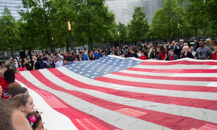 Firefighters, police and members of the public, hold the National 9/11 Flag at the ceremony for the  9/11 Memorial Museum  in New York City on Wednesday, May 21, 2014. The ceremony marked the opening of the National September 11 Memorial Museum. The flag was flying from a building near the World Trade Center on Sept. 11, 2001. It was later found shredded in the debris of ground zero and stitched back together seven years later by tornado survivors in Greensburg, Kansas.  (Benjamin Chasteen/Epoch Times)