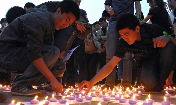 Chinese volunteers light candles at the Tangshan Earthquake Memorial Square during a memorial ceremony for the Sichuan earthquake victims on May 21, 2008. (Simon Lim/AFP/Getty Images)
