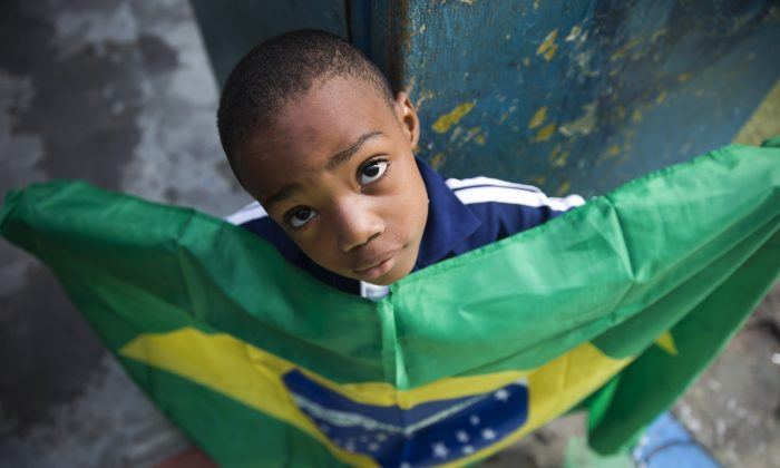A boy holds a representation of Brazil's national flag during a protest against public money spent on the preparations for the 2014 World Cup, at the Jacarezinho slum, in Rio de Janeiro, Brazil, on May 10, 2014. (AP Photo/Hassan Ammar)