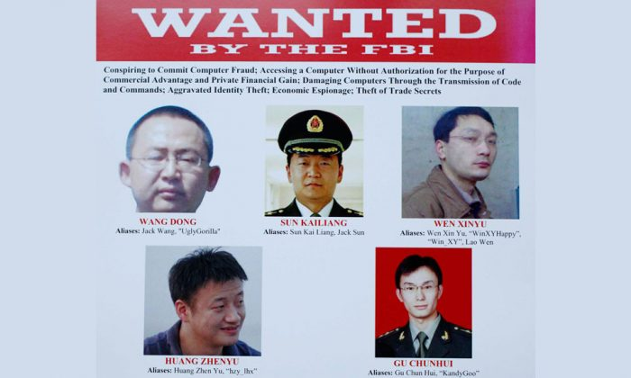 The five Chinese hackers that a U.S. grand jury has charged, are displayed on posters in Washington, on May 19, 2014. (AP Photo/Charles Dharapak)