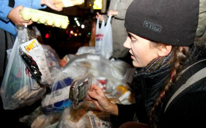 Cindy Rosin pulls food out of a garbage bag in front of a grocery store on Sixth Avenue and 12th Street. (Tara MacIsaac/The Epoch Times)