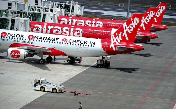 A ground crew man walks past a fleet of AirAsia's passenger jets on the tarmac of the new low cost terminal KLIA2 in Sepang, Malaysia, Friday, May 9, 2014. AirAsia on Friday began its full operations from KLIA2. (AP Photo/Joshua Paul)