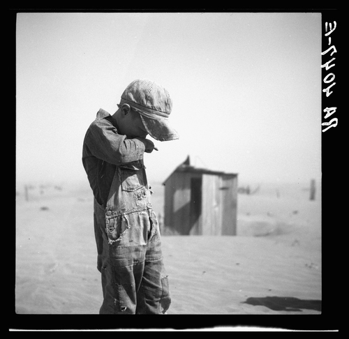 A boy protects his face from dust in Cimarron County, Okla., in 1936.