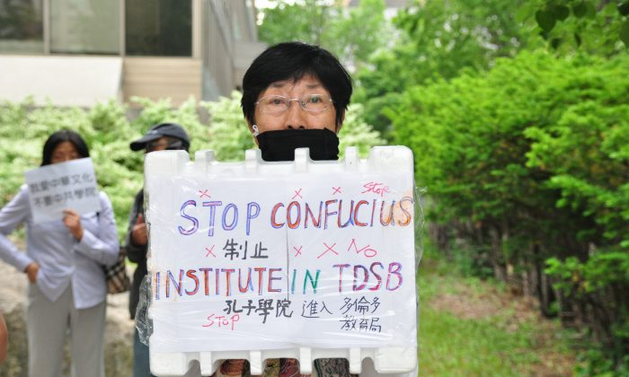 A demonstrator holds a sign to protest the Toronto District School Board's partnership with the Confucius Institute outside of the TDSB on June 11, 2014. (Allen Zhou/Epoch Times)