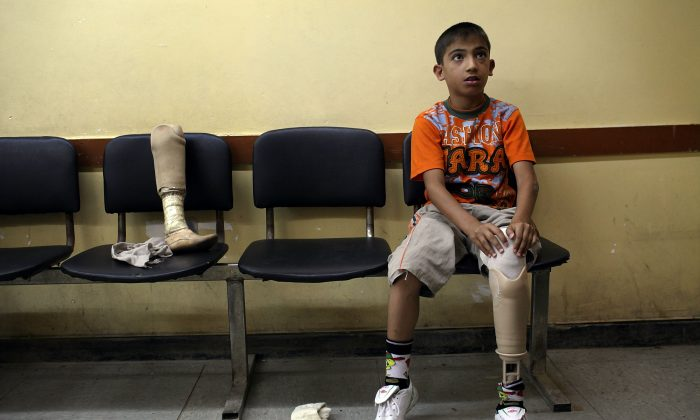 Ten-year-old Ali Mazin in Baghdad, Iraq, on July 11, 2011, tries on a new prosthetic leg after losing his in a car bombing in 2007. Residents of six Sunni-majority provinces in Iraq have staged peaceful sit-ins since late 2012. They accuse Iraqi Prime Minister Nouri al-Maliki of mass murder, blatant discrimination to favour Shias, and acting more like a criminal gang than a government during eight years in power. (Spencer Platt/Getty Images)