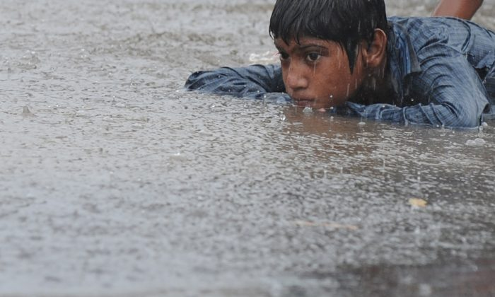 An Indian street child lies on a puddle of water along a road in New Delhi on June 16, 2013. (Sajjad Hussain/AFP/Getty Images)