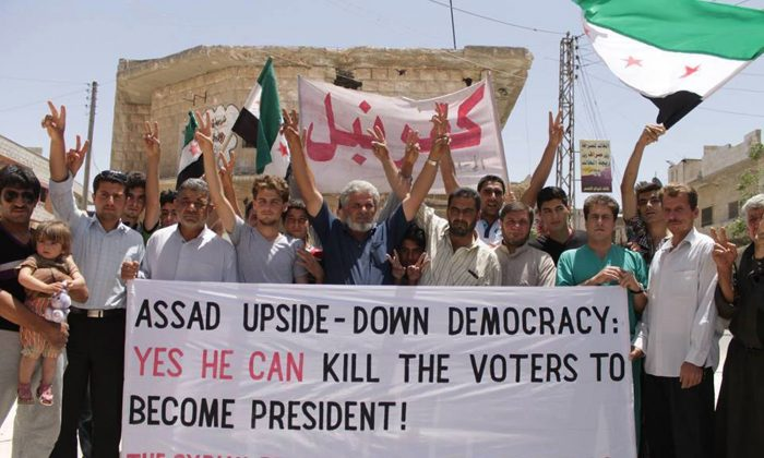 In this Friday, May 30, 2014, photo provided by an anti-Bashar Assad activist group Edlib News Network (ENN), which has been authenticated based on its contents and other AP reporting, protestors who oppose Syrian President Bashar Assad carry a banner during a demonstration at Kafr Nabil town in Idlib province, northern Syria. The country holds its first multi-candidate presidential election in nearly half a century on Tuesday, June 3, 2014. Despite government assertions the election could resolve the three-year civil war, there's no indication it will halt the violence or mend a bitterly divided nation. (AP Photo/Edlib News Network ENN)