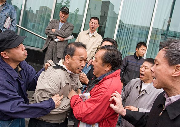 Flushing resident Edmond Erh was assaulted by a mob when he was volunteering at a table for the Global Service Center for Quitting the Chinese Communist Party in Flushing, New York on July 10, 2008 (Dayin Chen/Epoch Times)