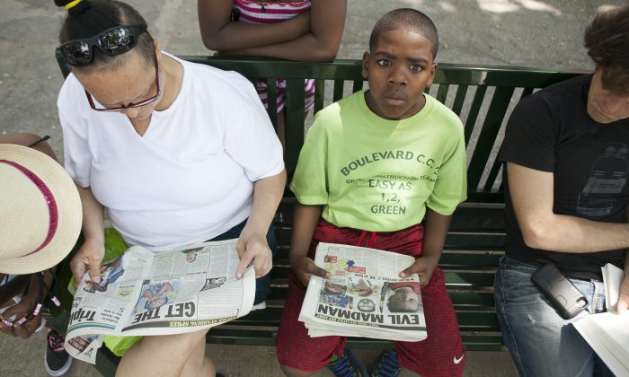 A boy looks up from a tabloid newspaper with an image of Prince Joshua Avitto, 6, a boy killed on June 1, at the Boulevard Houses project, in East New York, New York, on June 3, 2014. (Samira Bouaou/Epoch Times)