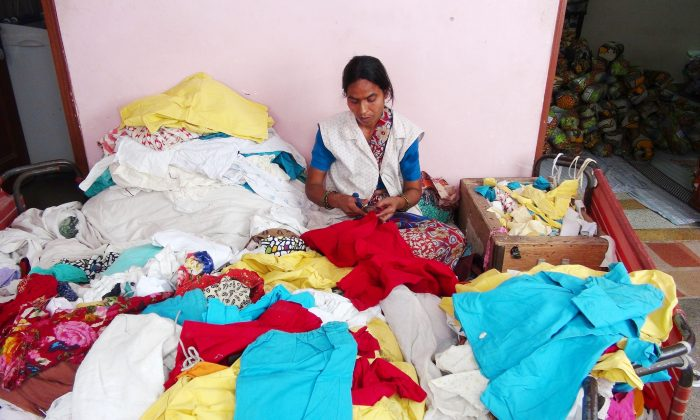An employee of Indian NGO Goonj sits amid discarded and sorted clothes at the organization's office in New Delhi on June 7, 2014. Goonj collects, washes, and mends discarded clothes and uses them as currency to pay poor villagers to build community infrastructure, an initiative called Clothes for Work. (Venus Upadhayaya/Epoch Times)