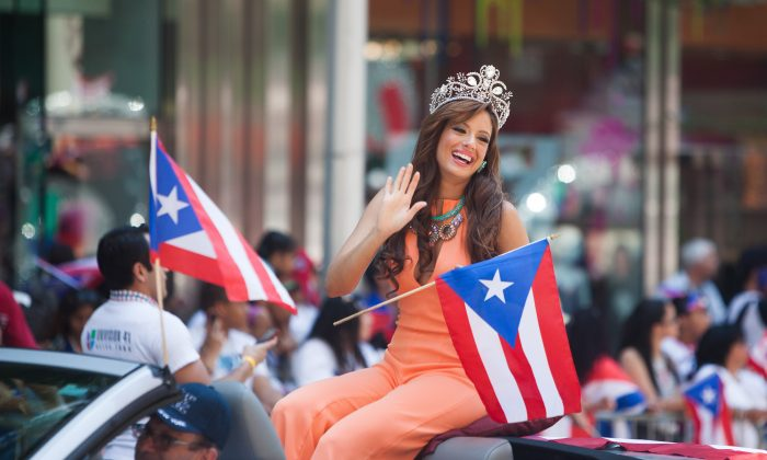 A women waves to onlookers at the National Puerto Rican Day Parade in Manhattan, on Sunday. (Petr Svab/Epoch Times)