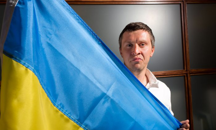 Ivan Rodichenko poses with the Ukrainian flag in Manhattan on June 11, 2014. Ivan Rodichenko fled to New York after being told he would die if he stayed in Ukraine, however, his asylum was rejected, so on June 12, he returned to Ukraine to meet his fate. (Benjamin Chasteen/Epoch Times)