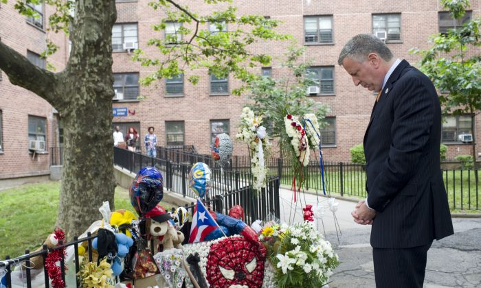 """Mayor Bill de Blasio pauses by the vigil of Prince Joshua """"PJ"""" Avitto at the Boulevard Houses in East New York, Brooklyn, on June 11. De Blasio later announced that security cameras would be installed in 49 public housing projects by the end of the year. (Rob Bennett/Mayor's Office)"""