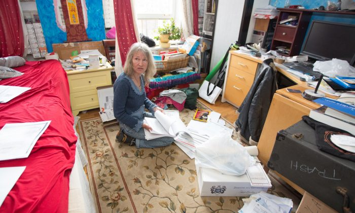Paula Gloria Tsaconas Barton sifting through court documents and letters in her Gramercy Park South co-op studio, June 11, 2014. Last year, while she was travelling, Tsaconas Barton got notice her apartment had been sold to someone else and is now facing eviction. (Laura Cooksey/Epoch Times)