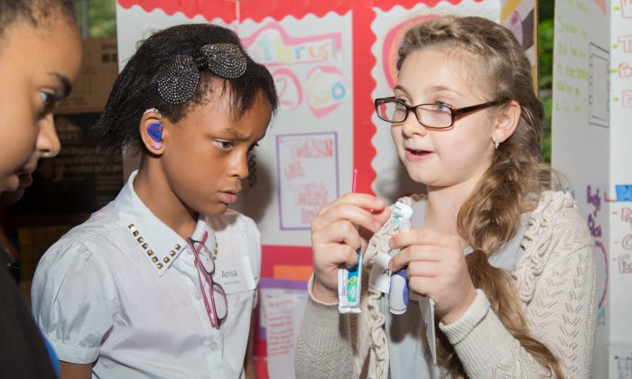 """Anastasia Svetlova, explains her invention called """"Toothbrush2Go,"""" which has toothpaste come out through the bristles of the toothbrush, to other students in Central Park, Manhattan, on June 13, 2014. (Benjamin Chasteen/Epoch Times)"""