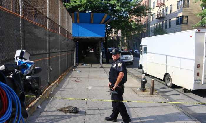 A police officer stands near blood stains from a fatal school stabbing near the Joseph Wade Middle School in the Bronx, June 18. (Brendon Fallon/Epoch Times)