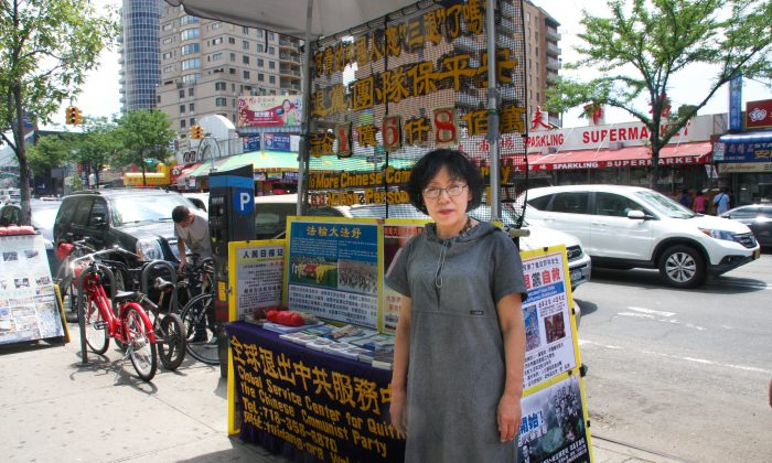 Li Ming stands near a booth to help Chinese people resign their membership from the Chinese Communist Party in Flushing, New York City, on June 23, 2014. Ming and several other residents in Flushing regularly experience discrimination and threats. (Joshua Philipp/Epoch Times)