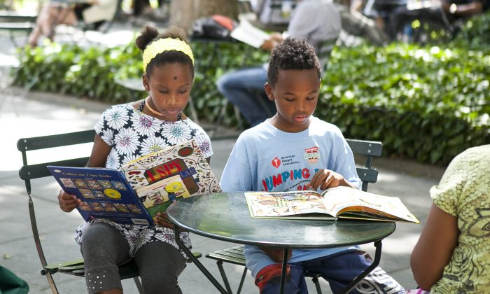 Two kids read at the Bryant Park Reading Room, in Manhattan, on June 25, 2014. (Samira Bouaou/Epoch Times)