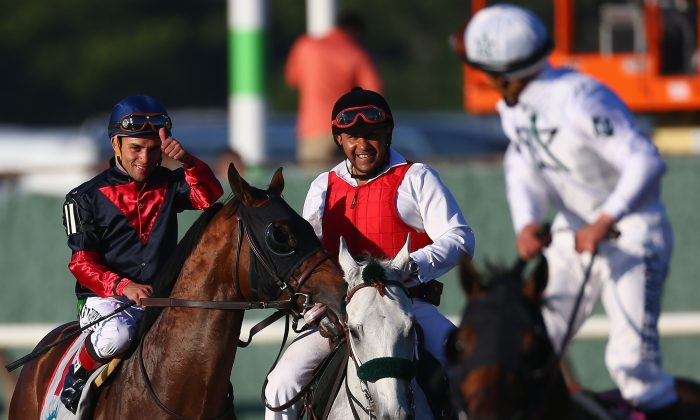 Horse Tonalist, ridden by Joel Rosario (L), after winning the 146th running of the Belmont Stakes at Belmont Park in Elmont, N.Y., on June 7, 2014.