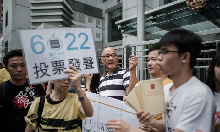 A demonstrator supporting the Occupy Central movement holds a placard asking residents to cast ballots for the June 22 referendum on three proposals outlining rules for the chief executive election, during a protest outside Beijing's representative office in Hong Kong on June 11, 2014. A website associated with that referendum was recently hacked. (Philippe Lopez/AFP/Getty Images)