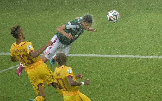 Mexico's forward Oribe Peralta (R) heads the ball past Cameroon's forward Eric Maxim Choupo-Moting (L) and midfielder Stephane Mbia (C) during the Group A football match between Mexico and Cameroon at the Dunas Arena in Natal during the 2014 FIFA World Cup on June 13, 2014.  (GABRIEL BOUYS/AFP/Getty Images)