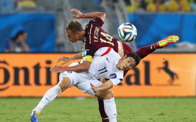 Lee Keun-Ho of South Korea and Vasily Berezutski of Russia compete for the ball during the 2014 FIFA World Cup Brazil Group H match between Russia and South Korea at Arena Pantanal on June 17, 2014 in Cuiaba, Brazil. (Photo by Elsa/Getty Images)
