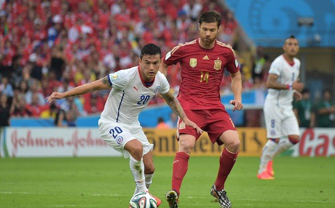 Chile's midfielder Charles Aranguiz and Spain's midfielder Xabi Alonso vie for the ball during a Group B football match between Spain and Chile in the Maracana Stadium in Rio de Janeiro during the 2014 FIFA World Cup on June 18, 2014. (GABRIEL BOUYS/AFP/Getty Images)