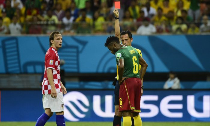 Portuguese referee Pedro Proenca Oliveira Alves Garcia (R) issues a red card to Cameroon's midfielder Alexandre Song (C) as Croatia's midfielder Ivan Rakitic (L) looks on during the Group A football match between Cameroon and Croatia at The Amazonia Arena in Manaus on June 18, 2014, during the 2014 FIFA World Cup. (PIERRE-PHILIPPE MARCOU/AFP/Getty Images)