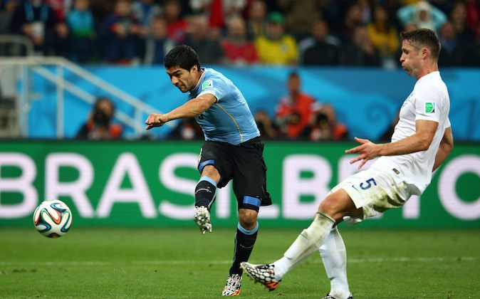 Luis Suarez of Uruguay scores his team's second goal against Gary Cahill of England during the 2014 FIFA World Cup Brazil Group D match between Uruguay and England at Arena de Sao Paulo on June 19, 2014 in Sao Paulo, Brazil. (Julian Finney/Getty Images)
