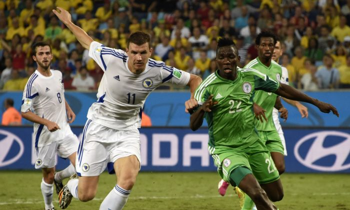 Bosnia-Hercegovina's forward Edin Dzeko (L) fights for the ball with Nigeria's defender Kenneth Omeruo during the Group F football match between Nigeria and Bosnia-Hercegovina at the Pantanal Arena in Cuiaba during the 2014 FIFA World Cup on June 21, 2014. (JUAN BARRETO/AFP/Getty Images)