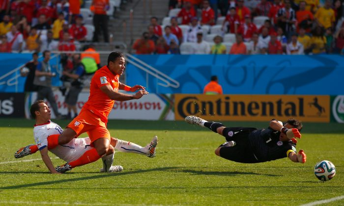 Memphis Depay of the Netherlands shoots and scores his team's second goal past goalkeeper Claudio Bravo of Chile during the 2014 FIFA World Cup Brazil Group B match between the Netherlands and Chile at Arena de Sao Paulo on June 23, 2014 in Sao Paulo, Brazil. (Photo by Clive Rose/Getty Images)